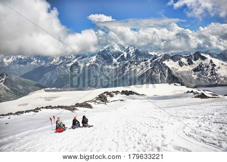 Climbers sit on the of Mount Elbrus and look at the Big Caucasian Ridge