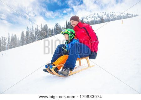 Father and his little son enjoying a sledge ride in famous ski resort in Tyrolian Alps Zillertal Austria