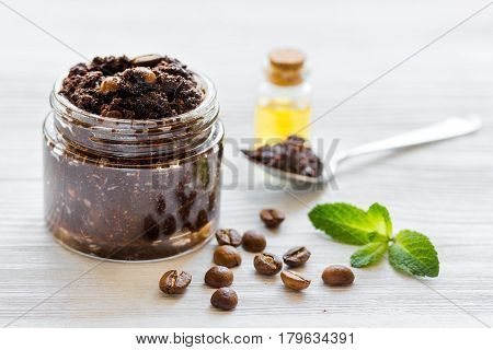 Organic body scrub of ground coffee with oil, beans and mint on white table background