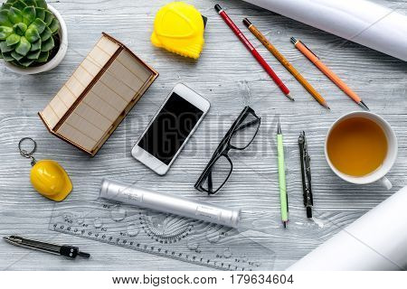 Architects workplace with constructor tools with cup of tea and mobile on light wooden table background top view