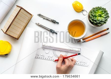 architect working desk with cup of tea, hands and project on white background top view