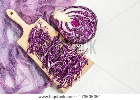 Chopped scotch kale or red cabbage on a cutting board and half of cabbage head on gauze napkin. It is used in dietary and vegetarian nutrition as well as for the prevention of cardiovascular disease