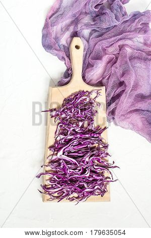 Chopped scotch kale or red cabbage on a cutting board on gauze napkin. It is used in dietary and vegetarian nutrition as well as for the prevention of cardiovascular disease. Vertical image