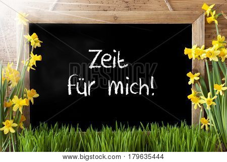 Blackboard With German Text Danke Means Thank You. Sunny Spring Flowers Nacissus Or Daffodil With Grass. Rustic Aged Wooden Background.