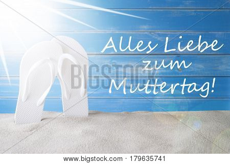 German Text Alles Liebe Zum Muttertag Means Happy Mothers Day. Sunny Summer Greeting Card With Sand And Flip Flops. Blue Vintage And Shabby Chic Wooden Background.