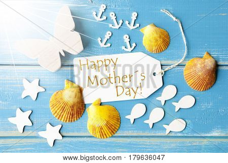 Flat Lay View Of Label With English Text Happy Mothers Day. Sunny Summer Greeting Card. Butterfly, Shells And Fishes On Blue Wooden Background