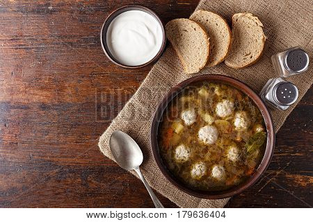 Soup with meatballs in a clay plate. The plate stands on a napkin next to it there is salt and bread space for text