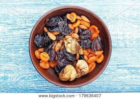 Dried figs dried apricots and prunes in a mix with almonds in a clay plate on a wooden table horizontal photo