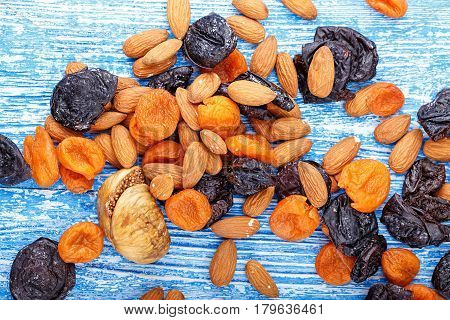 Dried fruits figs dried apricots and prunes in a mix with almonds scattered on a wooden table horizontal photo