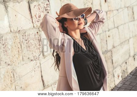 Young stylish woman wearing neutral blazer, hat and sunglasses walking on the city street in spring. Casual fashion, elegant look. Plus size model.