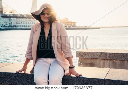 Young stylish woman wearing neutral blazer and hat walking on the city street in evening. Casual fashion, elegant look. Plus size model.