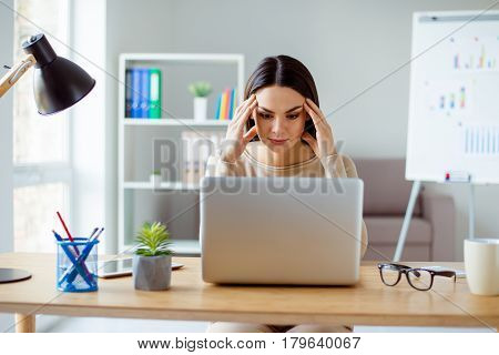 Thoughtful Pretty Tired Woman Sitting At The Table Touching Her Temlpes And Looking At Screem Of The