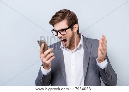 Angry Man Wearing Formal Wear  In Rage Screaming Into The Smartphone While Standing On Gray Backgrou