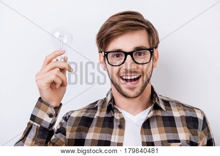 Portrait Of Young Smart Man With Great Idea Holding Bulb Of Lamp And Excited Open Mouth