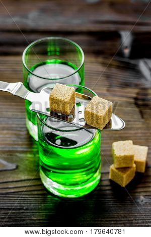 green absinthe shots with sugar cubes on wooden bar table background
