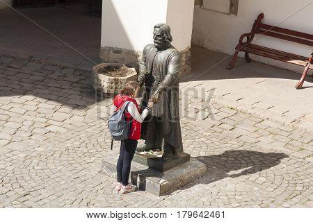 Girl making a wish to statue of prince Podolsky Fedir Koryatovych (1331-1414) in castle Palanok Mukachevo Ukraine photo: MUKACHEVOUKRAINE - APRIL 12017