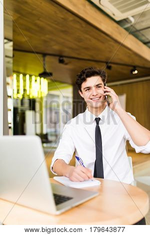 Smiling Young Businessman Sitting Behind His Desk With Laptop And Talking On Mobile Phone In Office