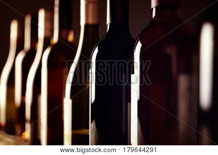 Bottles of old aged wine collection in a row in winery cellar