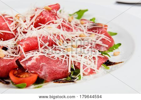 Meat platter with cheese, corn, tomatoes and arugula on plate. Close-up, white background.