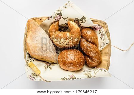Khachapuri, bagel, wicker bun and round bun in basket. Top view, white background.
