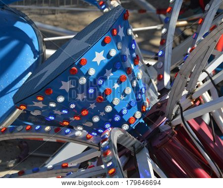 red white and blue carnival amusement fair  ride spokes blue sky background