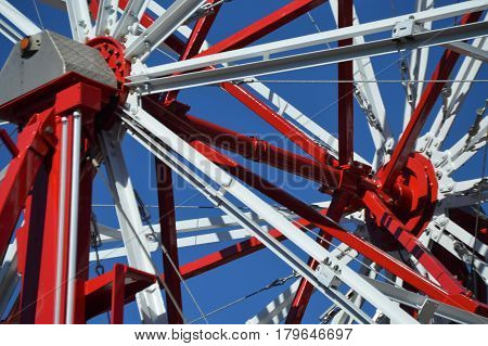 red and white carnival ride spokes with blue sky background