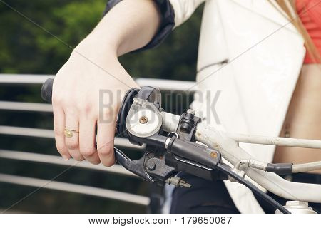 Female Sitting On A Motorcycle, Hand On Grip, Outdoors.