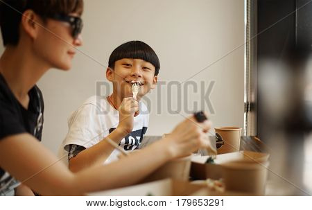 Asian mother & son eating lunch in a restaurant
