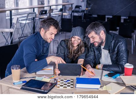 Video conference of young smart team. Group of modern people speaking on video conference. Working environment with laptop coffee notepads and stationery.