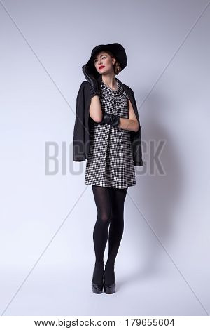 Beautiful young woman with red lips make-up in retro black and white dress, hat, jacket and leather gloves standing on grey background.