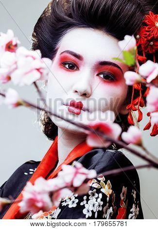 young pretty geisha in black kimono among sakura, asian ethno close up concept
