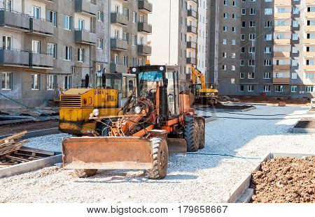SAMARA RUSSIA - MAY 29 2016: Grader works on laying gravel on the road at the construction site
