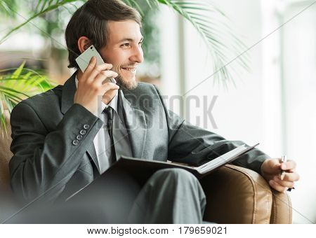 Confident businessman in office talking on the phone.