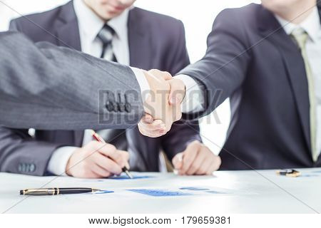 closeup of handshake of business partners on the background of a lawyer and financial documents