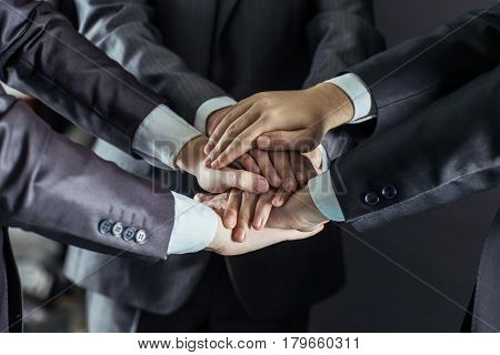 close-up of hands of business teams, stacked one on another.photo on a black background and has space for your text.