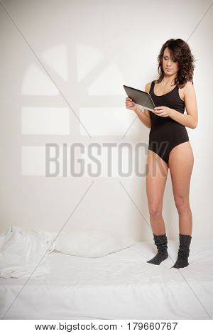 Sexy Lazy Girl With Tablet Touchpad In Bedroom