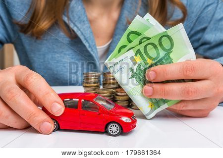Businesswoman With Money And Toy Red Car In Hands