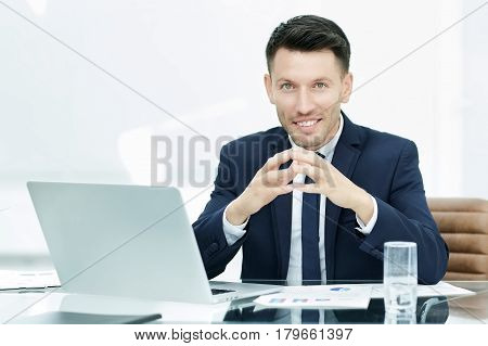 businessman at the workplace working with financial documents. in the workplace is an open laptop and a glass of water