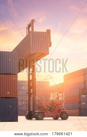 Forklift Truck Lifting Cargo Container In Shipping Yard Or Dock Yard Against Sunrise Sky With Cargo