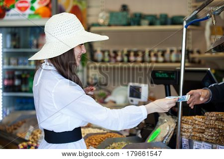 Smiling woman in a store is buying products