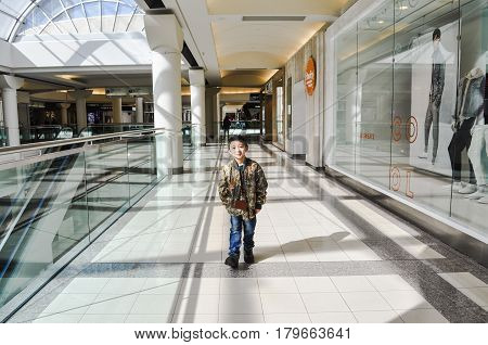 April 4 2017-Little boy walking by it's own inside Metropolis at Metrotown Mall Burnaby,BC Canada