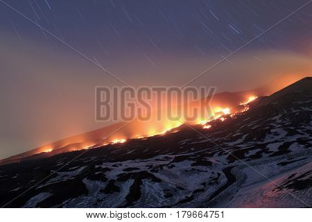 ETNA PARK, SICILY - MARCH 30, 2017: star trails on red lava river from the mouth opened at the base of the New SouthEast Crater, at an altitude of 3.010 meters; it flow on old lava covered with snow