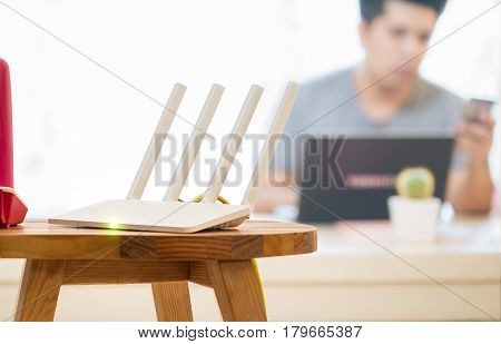 closeup of a wireless router and a man using smartphone on living room at home