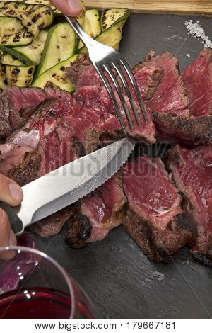 Cutting and eating grilled T-bone sliced beef steak and vegetables.