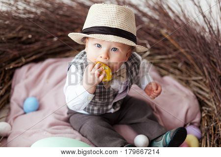 Baby in Easter nest with eggs in in a suit and hat. Easter holiday concept: nest with baby.