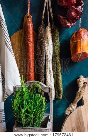 Variety of Spanish cured meat products charcuterie fresh rosemary wood cutting board hanging on hooks pantry