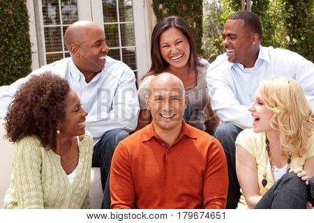 Diverse ethnic group of people smiling outside.