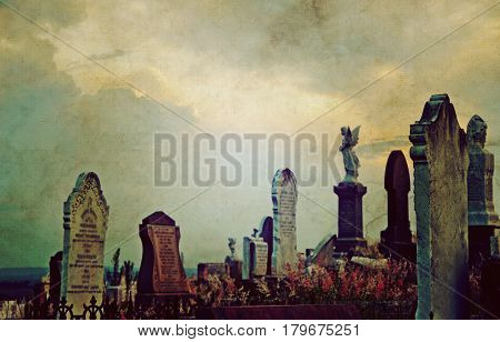 Gothic cemetery landscape at twilight with old headstones and angels under a luminous, dramatic sky. Vintage grunge textured image.