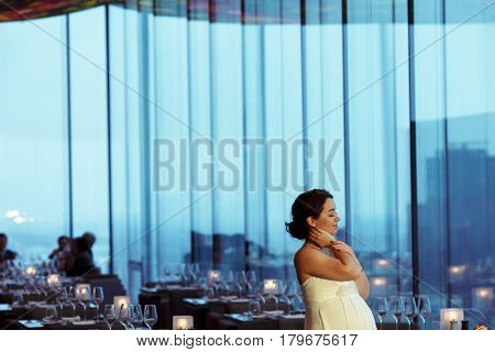 Pregnant Bride Holds Her Nack Daydreaming In An Empty Cafe