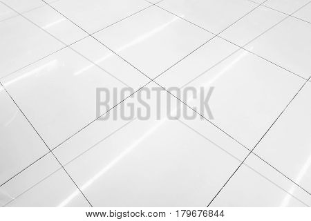 Flooring tile background and reflection of luminaire.